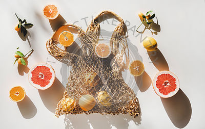 Summer net bag with fresh fruits over white background
