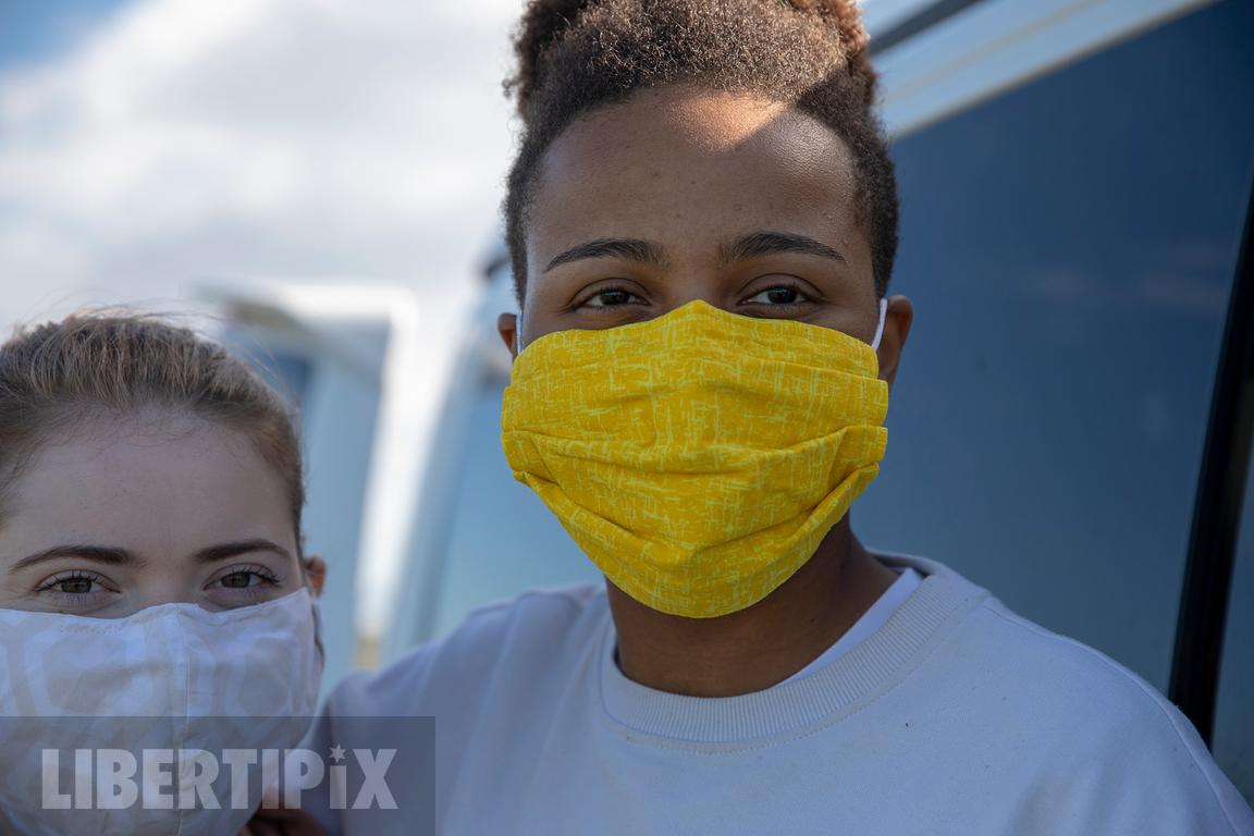 A LGBTQ+ STOCK PHOTO OF AN AUTHENTIC LESBIAN COUPLE WEARING MASKS TO PROTECT FROM COVID.