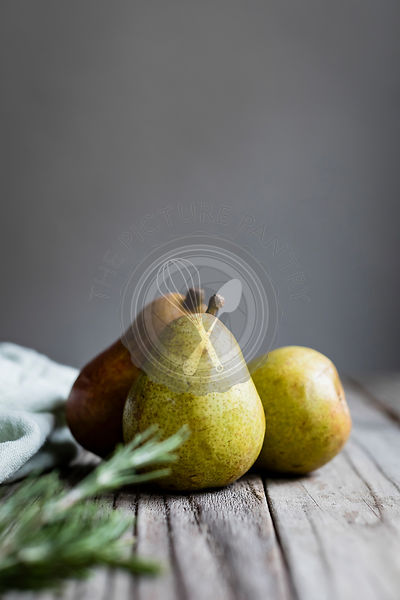 Ripe green pears on a rustic wooden table