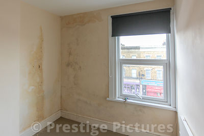 Damp walls in home with local shops out of the window