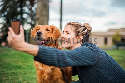 A woman and golden retriever take a selfie together