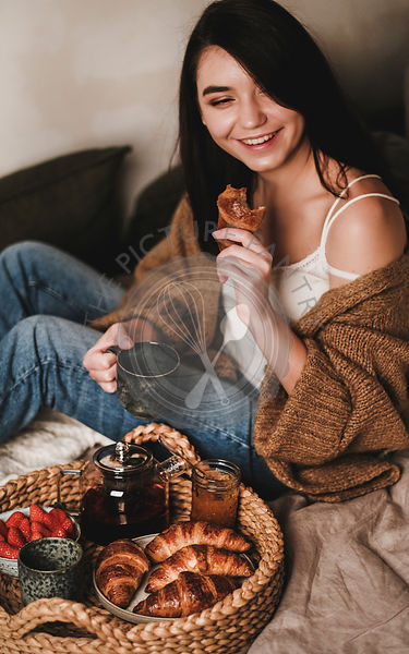 Young beautiful smiling brunette woman enjoying tasty breakfast in bed