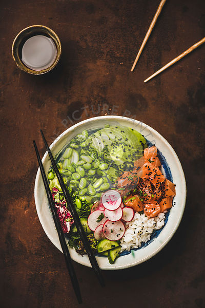 Hawaiian salmon poke bowl with vegetables, greens, rice, soy sauce