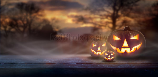 Mist rolling in over the spooky glow of Jack O' Lanterns on the right hand side of a wooden bench in a forest at dusk.