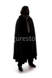 A mystery man in a big cloak standing and looking away – shot from eye level.