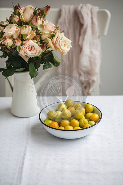 Green plums in a bowl on a kitchen table