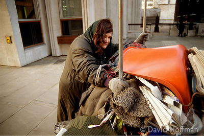 Homeless mentally ill woman pushing a trolley loaded with old clothes, furniture, bric-a-brac, clothing, blankets, rubbish & ...