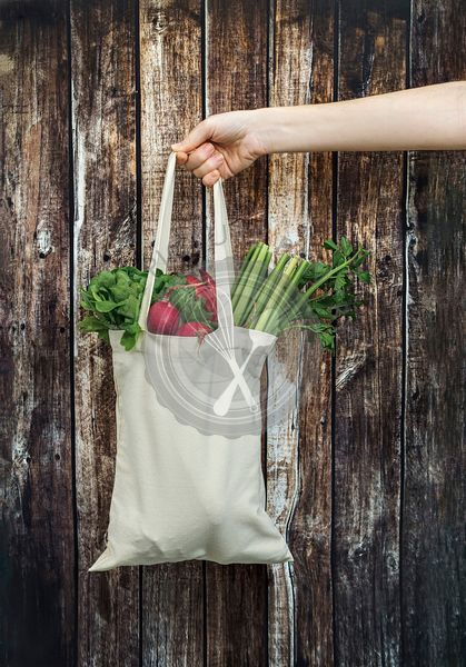 Female hand holds cotton bag with fresh vegetables