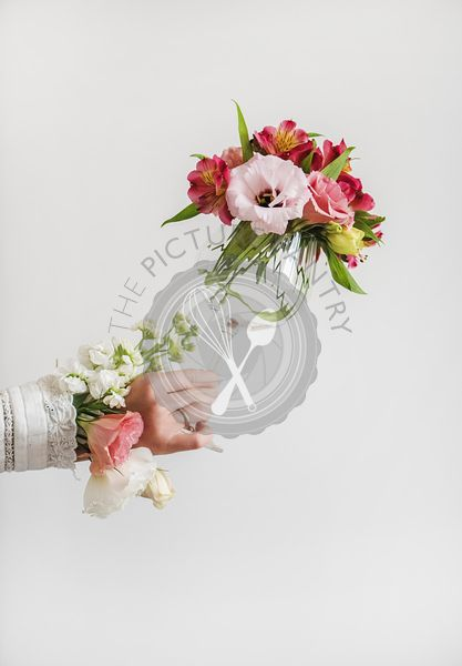 Female hand holding bouquet of blooming flowers in glass