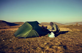 A female hiker preparing to make a hot drink beside their tent that's pitched on a mountain summit at sunrise at Rampsgill He...