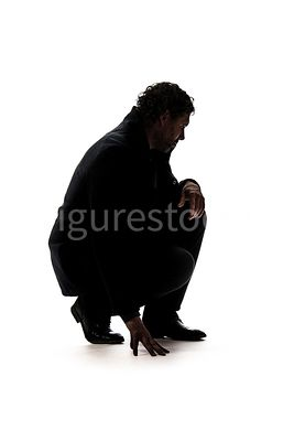 A crouching mystery man, looking down, in silhouette – shot from low level.