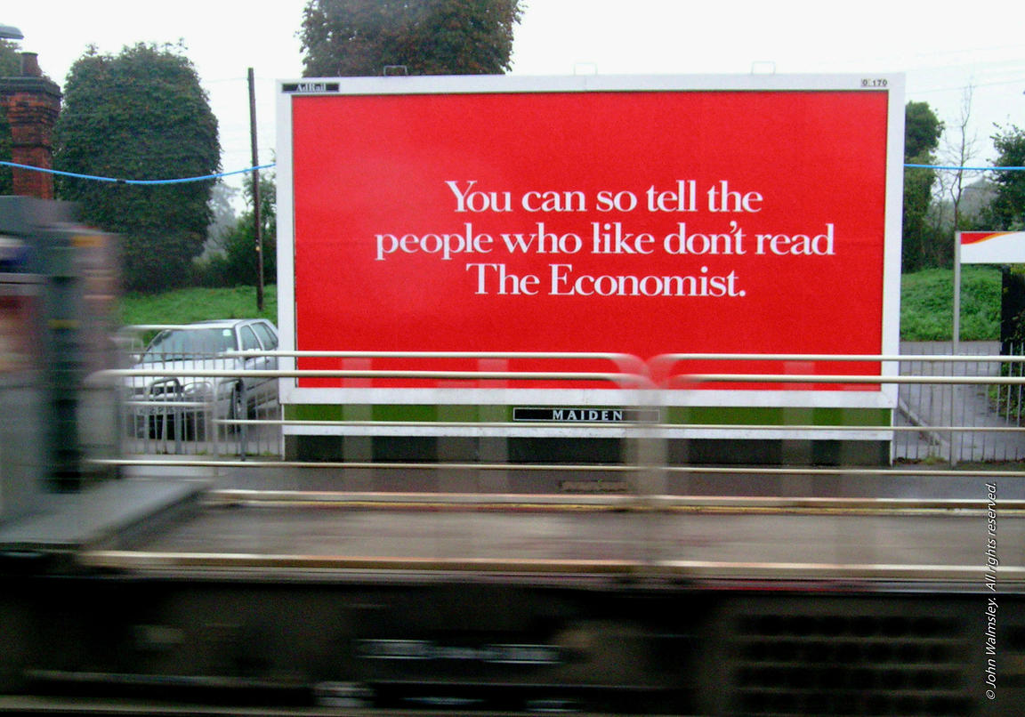 #27336  Really bright billboard for 'The Economist' at a small local rail station in Surrey