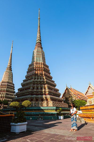 Asian woman in front of stupa, Wat Pho temple, Bangkok