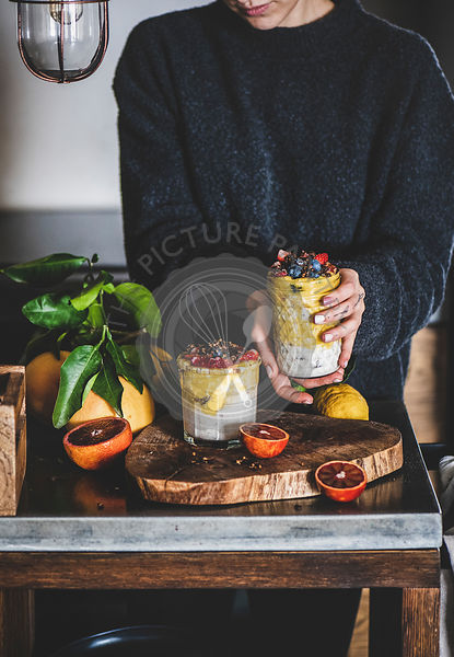 Woman holding glass of muesli with mango smoothie and granola