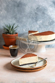 White chocolate cheesecake dusted with cocoa powder on the plate