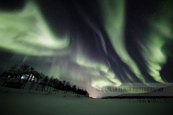Geomagnetic storm above a restaurant on the shore of the Teno River in Lapland