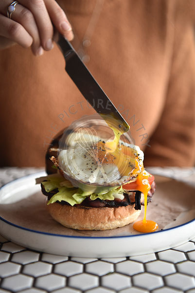 Runny egg on breakfast burger , being cut with a knife