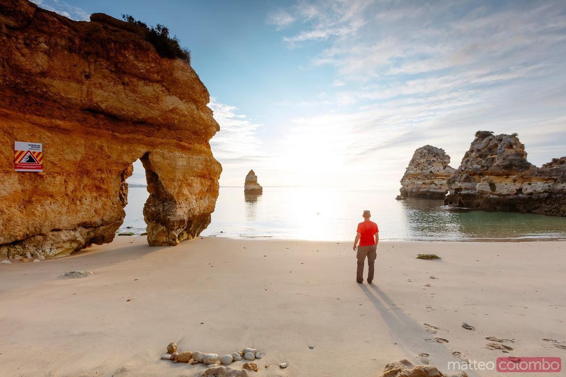 Man at the beach admiring sunrise, Algarve, Portugal