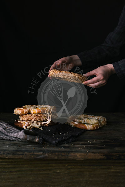 A Women's Hands Taking Bagel on a Black Background