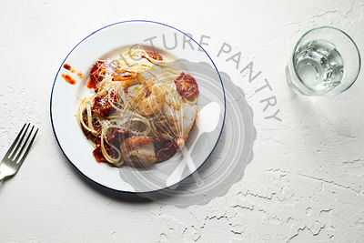 Spaghetti with pan seared prawns, oven roasted tomatoes and parmesan, on an enamel plate, with a fork and glass. White backgr...