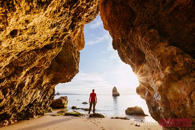 Man enjoying sunrise from a cave, Algarve, Portugal