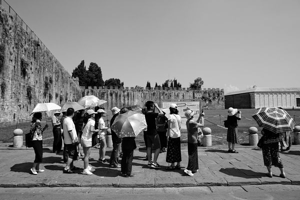 A group of tourists inside the Pisa Tower sightseeing area.