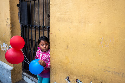A girl with balloons in the street