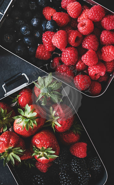 Flat-lay of fresh berries in lunchboxes over dark background