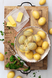 White potatoes with butter and parsley on a wooden chopping board.