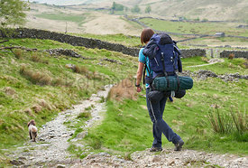 A female hiker, backpacker, and their dog walking along a mountain trail in the English Lake District.
