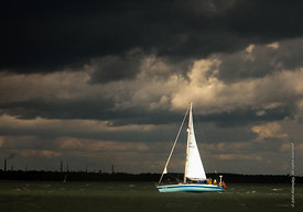 #61936  Sailing boat urgently heading for port to avoid the gathering cumulus storm clouds at sea.