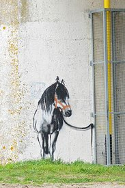 An airbrush graffiti painting on a bridge pillar , of a riding horse attached to the downspout
