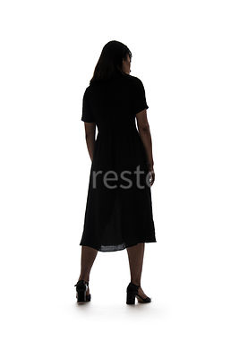 A silhouette of a woman in a dress - shot from low level.