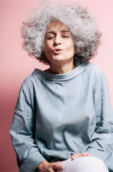 A Beautiful Mature Woman With Big Curly Grey Hair Captured With A Fun And Candid Expression On Her Face