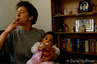 Single mother holding her child as she smokes a cigarette.