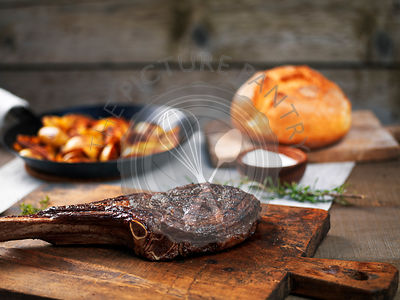 Grilled angus beef tomahawk steak on a cutting board with roasted potatoes in wrought iron pan