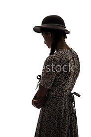 A silhouette of a 1940's girl in a summer dress and hat – shot from eye-level.