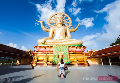 Asian woman praying in front of the Big Buddha, Ko Samui, Thailand