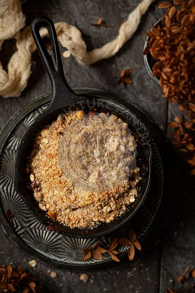 A single-serve cast iron skillet holding freshly baked pear and chocolate crumble