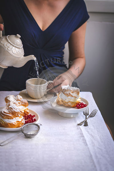 Cream puffs pastry and woman pouring a cup of tea