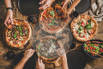 Flat-lay of people having pizza party dinner with red wine