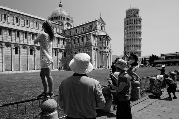 "Tourists near the Pisa Tower taking a common photo where you appear to be ""preventing the leaning tower from falling""."