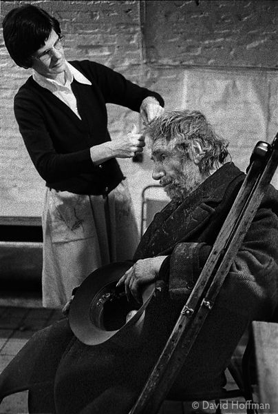 F62-26 Bobbie Beecroft cutting Mr Sheridan's hair in the wet crypt at St Botolph Church, 1978.