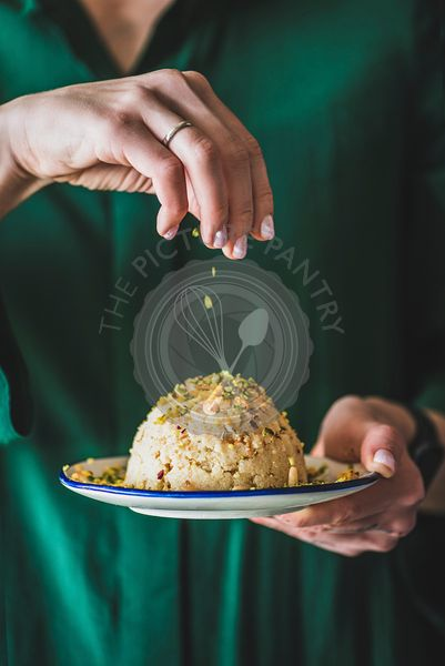 Woman holding plate with Turkish semolina helva with pistachio