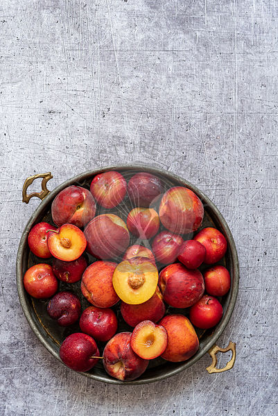 Metal tray with fresh plums and peaches