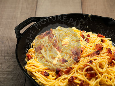 "Italian ""Spaghetti alla carbonara"" with bacon, egg and pepper cooked and served in a cast iron pan on a wooden table"