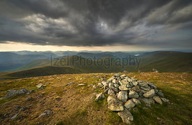 Dark clouds gather over the mountains in the evening just before sunset from the summit of Rampsgill Head with Rest Dodd, The...