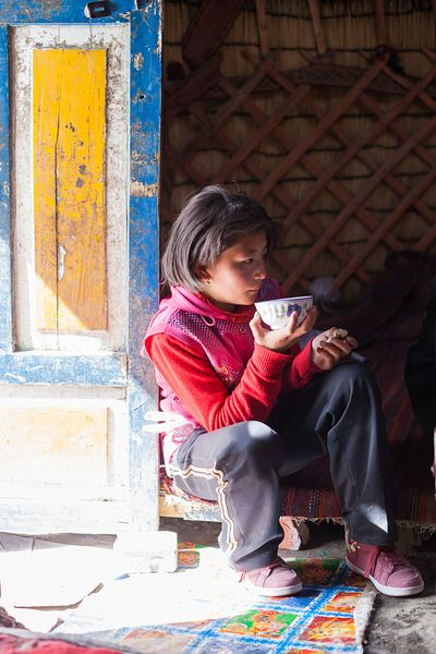 Young kyrgyz girl drinking tea inside a yurt