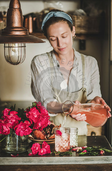 Young woman pouring rose lemonade to glasses in kitchen