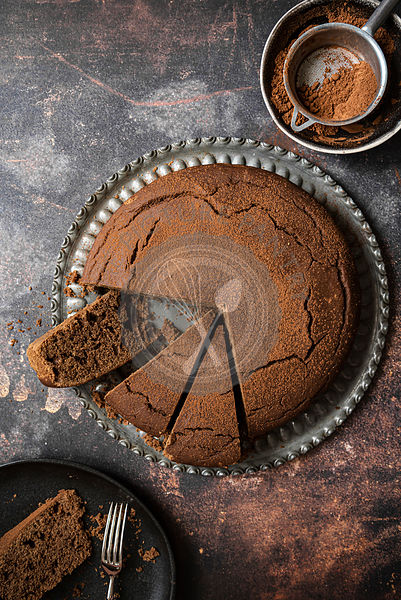 Chocolate cake slices with sifter and cocoa powder